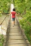 Muchacha que camina en un puente de madera sobre un río Fotos de archivo
