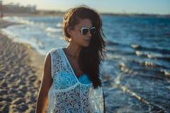 Muchacha que camina en una playa ventosa imagenes de archivo