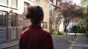 Muchacha que camina entre la pared de ladrillo metrajes