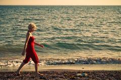 Muchacha que camina a lo largo de la playa Fotos de archivo libres de regalías