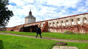 Muchacha que camina a lo largo de las paredes históricas viejas del castillo y de una fortaleza militar con la arquitectura de 16 metrajes