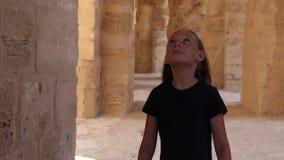 Muchacha que camina que mira para arriba y alrededor en el pasillo con los arcos y el color del beige de las columnas almacen de metraje de vídeo