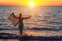 Muchacha que camina por el mar en el concepto de las vacaciones de la puesta del sol Imagen de archivo