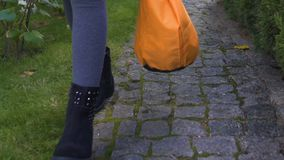 Muchacha que camina solamente con el bolso del truco o de la invitación en la víspera espeluznante de Halloween, tradiciones metrajes