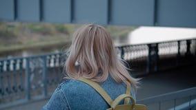 Muchacha que camina a través de la ciudad de igualación abajo en la transición debajo del puente Primer en el movimiento metrajes