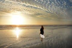 Muchacha que camina y que goza en la playa hermosa en la salida del sol Imagen de archivo