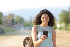 Muchacha que camina y que usa un teléfono elegante en una ciudad Foto de archivo libre de regalías