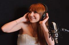 Muchacha cantante en auriculares. Fotografía de archivo