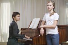 Muchacha que canta como profesor Play The Piano Foto de archivo libre de regalías