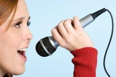 Muchacha que canta con el micrófono Foto de archivo libre de regalías