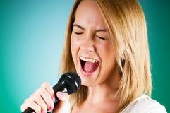 Muchacha que canta con el micrófono contra gradiente Foto de archivo libre de regalías