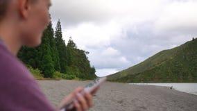 Muchacha que canta en la orilla del lago en la naturaleza que escucha la música en un smartphone metrajes