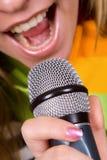 Muchacha que canta en micrófono Imagen de archivo