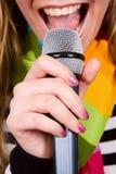 Muchacha que canta en micrófono Fotografía de archivo