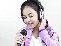 Muchacha que canta en su micrófono Fotografía de archivo