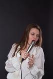 Muchacha que canta en un micrófono Foto de archivo libre de regalías
