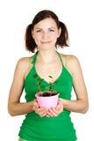 Muchacha que celebra la planta potted y la sonrisa Imagen de archivo