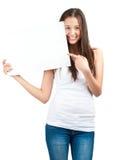 Muchacha que celebra un letrero y señalar en blanco Imágenes de archivo libres de regalías