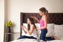 Muchacha que cepilla su pelo de los mejores amigos en dormitorio Imagen de archivo libre de regalías