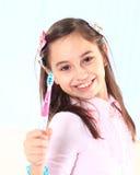 muchacha que cepilla sus dientes. Foto de archivo