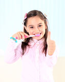 Muchacha que cepilla sus dientes. Imagenes de archivo