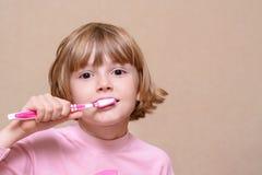 Muchacha que cepilla sus dientes con un cepillo de dientes Fotografía de archivo libre de regalías