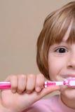 Muchacha que cepilla sus dientes con un cepillo de dientes Foto de archivo