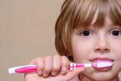 Muchacha que cepilla sus dientes con un cepillo de dientes Fotos de archivo