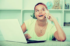 Muchacha que charla en el teléfono y que mecanografía en el ordenador portátil Fotos de archivo
