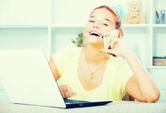 Muchacha que charla en el teléfono y que mecanografía en el ordenador portátil Imagenes de archivo