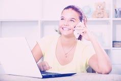 Muchacha que charla en el teléfono y que mecanografía en el ordenador portátil Foto de archivo libre de regalías