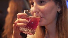 Muchacha que charla y que bebe el cóctel alcohólico del vidrio en barra almacen de metraje de vídeo