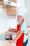 Muchacha que cocina en cocina moderna Imagen de archivo libre de regalías
