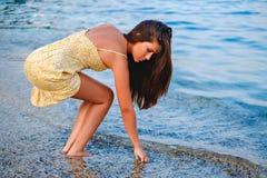 Muchacha que coge conchas marinas en la playa imagenes de archivo