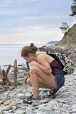 Muchacha que coge conchas marinas en la playa Fotos de archivo libres de regalías