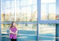 Muchacha que coloca la escuela cercana y que mira para arriba Fotos de archivo libres de regalías