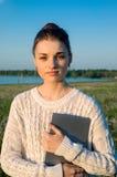 Muchacha que coloca y que sostiene una tableta Imagenes de archivo