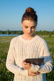 Muchacha que coloca y que sostiene una tableta Fotos de archivo