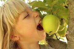 Muchacha que come Apple en árbol Imagen de archivo
