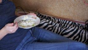 Muchacha que come el alimento biológico sano que miente en el sofá en casa almacen de metraje de vídeo