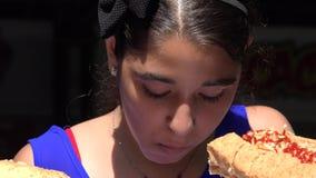 Muchacha que come el almuerzo del perrito caliente metrajes