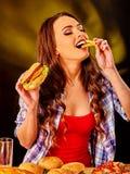 Muchacha que come el bocadillo grande y las patatas fritas Imagenes de archivo