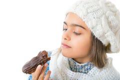 Muchacha que come el buñuelo azucarado Imagenes de archivo