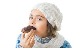 Muchacha que come el buñuelo azucarado Fotografía de archivo