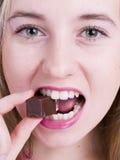 Muchacha que come el chocolate Imagen de archivo libre de regalías
