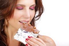 Muchacha que come el chocolate Fotos de archivo