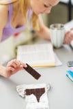 Muchacha que come el chocolate mientras que estudia en cocina. Primer Fotos de archivo libres de regalías