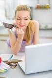Muchacha que come el chocolate y que mira en ordenador portátil Fotos de archivo libres de regalías