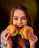 Muchacha que come el emparedado grande Imagen de archivo