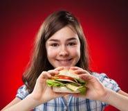 Muchacha que come el emparedado grande Fotos de archivo